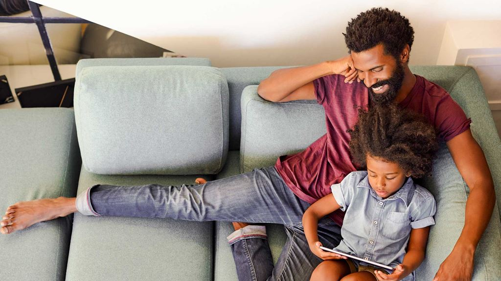 Father and child relaxing on a sofa reading a book